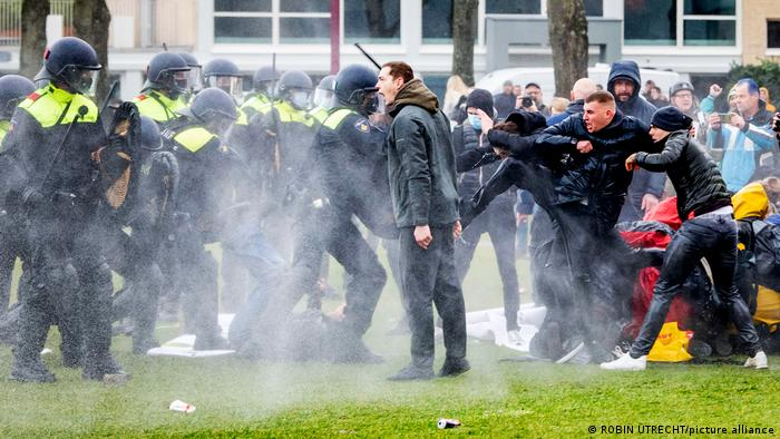 Police clashing with protesters at a rally against coronavirus restrictions