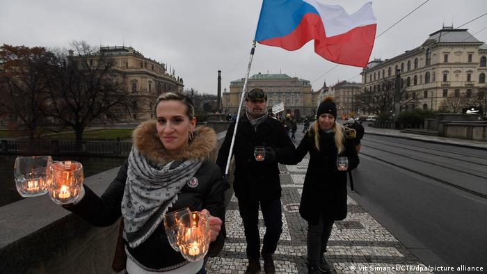 Czechs carry beer mugs with vigil candles to protest coronavirus protection measures