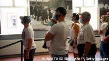 Besucher mit Corona-Schutzmasken in der Gedenkstätte des ehemaligen deutschen Nazi-Vernichtungslagers Auschwitz-Birkenau nahe der polnischen Stadt Oświęcim am 1. Juli 2020, dem Tag der Wiedereröffnung. Zuvor war die Gedenkstätte wegen Corona bzw. COVID-19 das erste Mal seit 1947 geschlossen, die Besucherzahl 2020 schrumpfte im Vergleich zu 2019 auf ein Fünftel