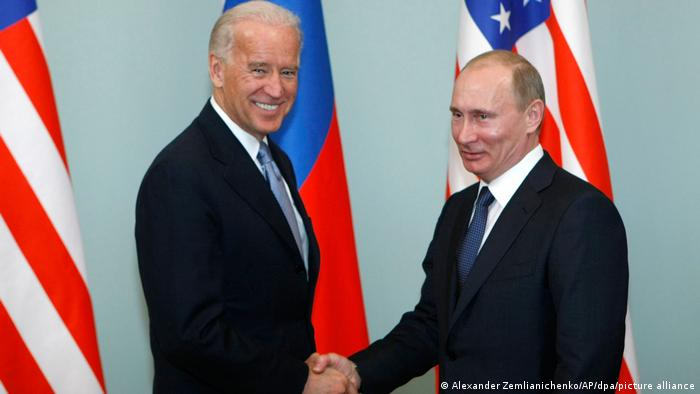 Joe Biden (kiri) dan Vladimir Putin (kanan) berjabat tangan di sebuah pertemuan pada tahun 2011