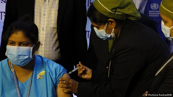 A health worker is vaccinated in Dhaka, Bangladesh