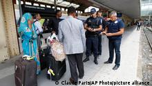 Police officers check identity documents at the Saint-Charles train station