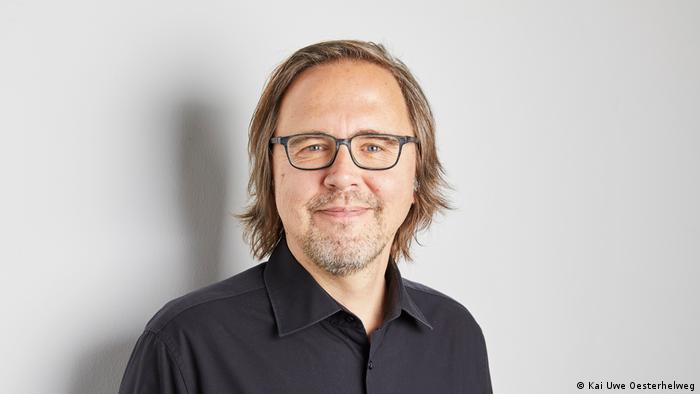 Portrait des Studienautoren Thorsten Hellmann im schwarzen Hemd, der in die Kamera lächelt