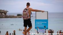 210126 -- SYDNEY, Jan. 26, 2021 -- A man stands beside a social distancing notice board at Bondi beach in Sydney, Australia, on Jan. 26, 2021. Beach lovers were warned to keep safe in the sea as heatwave continued to sweep states in east Australia. The Bureau of Meteorology also warned about severe heatwave conditions in isolated areas of inland Queensland and northern New South Wales NSW from Monday to Wednesday. AUSTRALIA-SYDNEY-BEACH BaixXuefei PUBLICATIONxNOTxINxCHN