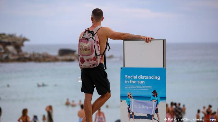 A man stands beside a social distancing notice board at Bondi beach in Sydney, Australia