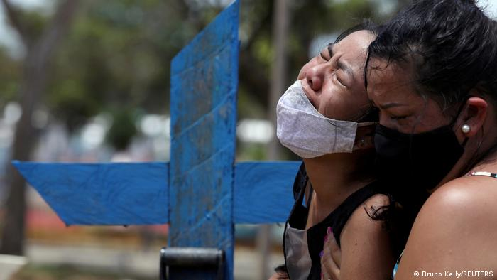 Kelvia Andrea Goncalves, 16, is supported by her aunt Vanderleia dos Reis Brasao, 37, as she reacts during the burial of her mother Andrea dos Reis Brasao