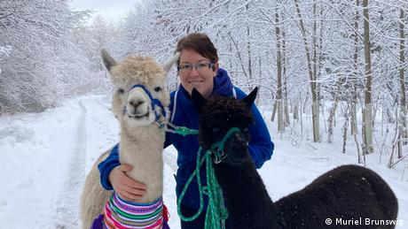 Black Forest, Germany, woman with two alpacas in a snow covered forest