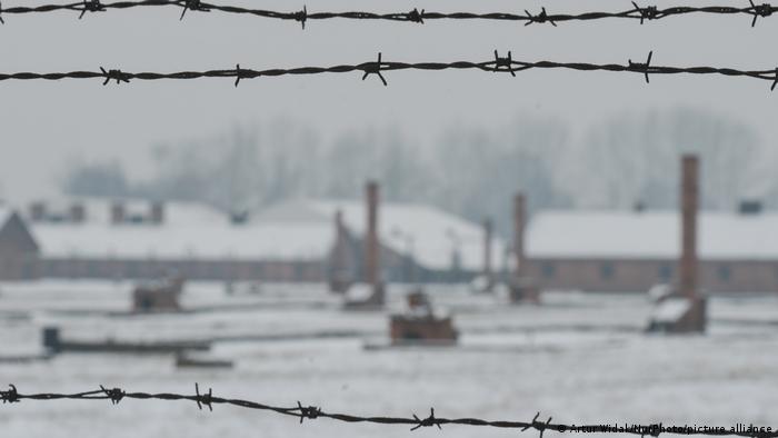 Cerca de arame farpado em primeiro plano. Ao fundo, desfocado, o campo de concentração coberto de neve.