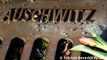 A flower is seen next to the word 'Auschwitz' at a memorial on a platform at the Berlin-Grunewald train station