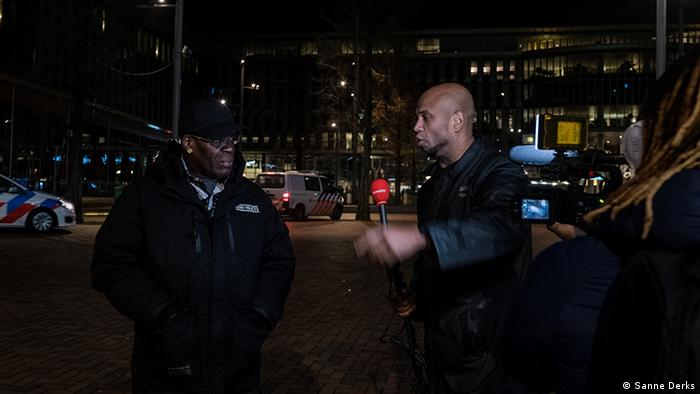 Journalist interviewing a man about the anticipated riots