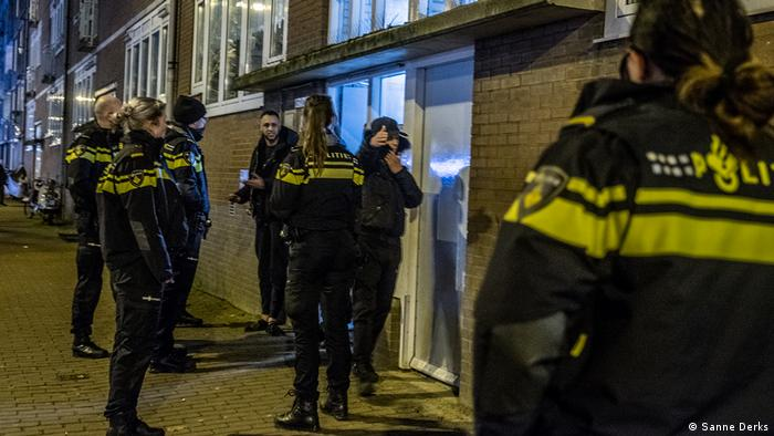 A team of police in Amsterdam speaking to two men