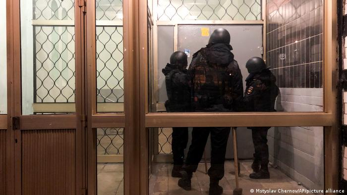 Police stand in front of a door of the apartment building where Oleg Navalny lives