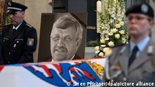 Das Konterfei von Walter Lübcke (CDU) ist hinter einem Bundeswehrsoldaten am Sarg bei einem Trauergottesdienst in der Martinskirche zu sehen. Ein halbes Jahr nach dem Mord an Lübcke steht die Anklage gegen die drei Tatverdächtigen kurz bevor. +++ dpa-Bildfunk +++