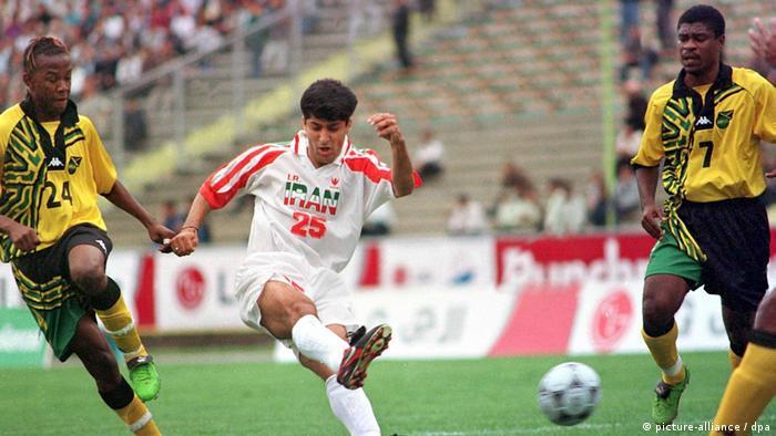 صحنهای از شوت مهرداد میناوند در دیدار تدارکاتی میان تیمهای ملی ایران و جامائیکا در آوریل ۱۹۹۸ که با پیروزی ۲ بر یک ایران پایان یافت. ایران و جامائیکا هر دو از شرکتکنندگان در دور نهایی مسابقات جام جهانی ۱۹۹۸ فرانسه بودند.