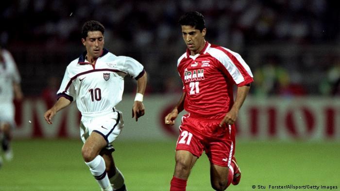 تلاش یکی از بازیکنان تیم ملی آمریکا برای مهار مهرداد میناوند در پیکار ایران و آمریکا در دور گروهی مسابقات جام جهانی فرانسه در تاریخ ۲۱ ژوئن ۱۹۹۸.