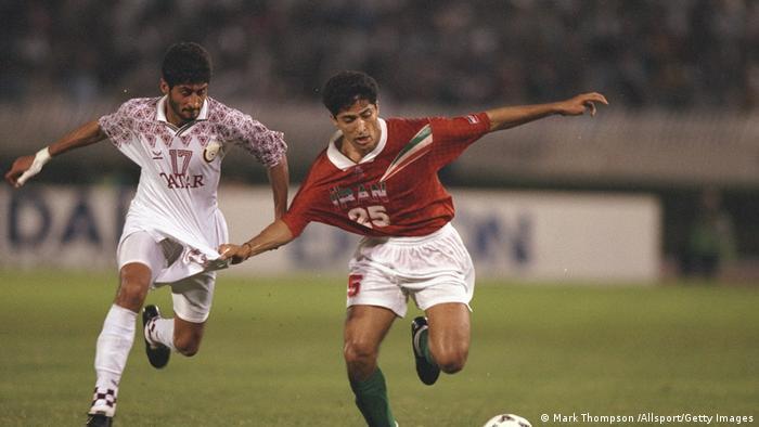 نبرد تن به تن مهرداد میناوند با یکی از بازیکنان تیم ملی فوتبال قطر در مصاف دو تیم در نوامبر ۱۹۹۷، در چارچوب مسابقات مقدماتی جام جهانی ۹۸ فرانسه.