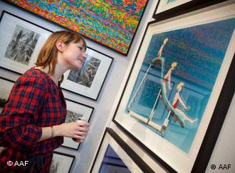 A woman looks at a work of art at the Affordable Art Fair in Paris