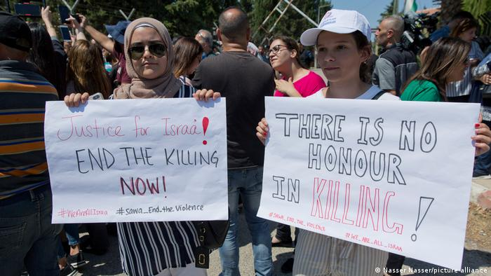 Two Palestinian women hold placards during a rally protesting honor crimes.