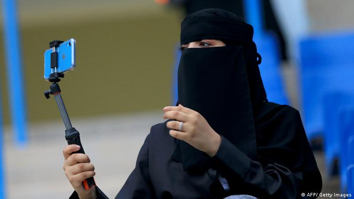A Saudi woman football fan uses a selfie stick to film herself on her phone.