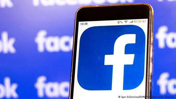 In this photo illustration, a Facebook logo is seen displayed on smart phone on a background of Facebook banner.