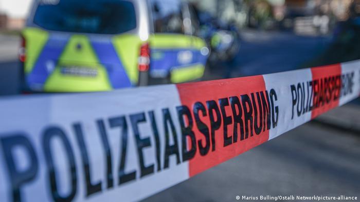 Faixa branca e vermelha impede a passagem de pessoas. Ao fundo, desfocada, está uma viatura da polícia, que na Alemanha tem as cores azul e amarela.