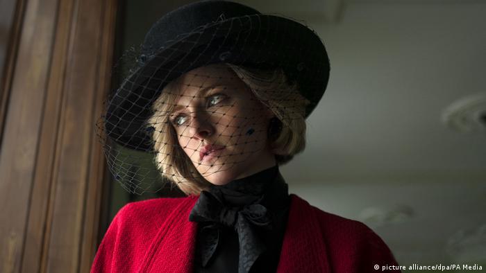 Kristen Stewart, mit Hut und Schleier, schaut mit dem typisch scheuen Diana-Augenaufschlag aus einem Fenster