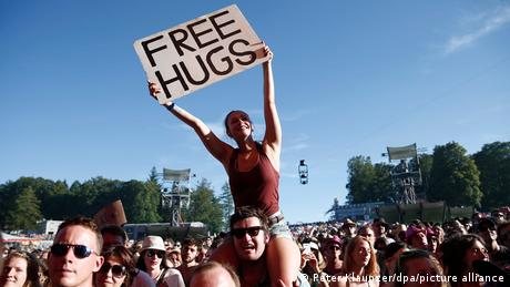 A woman holding a Free Hugs sign at a festival