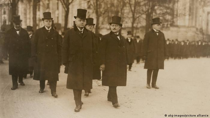 Men in top hats wear black in a funeral procession