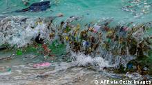 TOPSHOT - A wave carrying plastic waste and other rubbish washes up on a beach in Koh Samui in the Gulf of Thailand on January 19, 2021. (Photo by Mladen ANTONOV / AFP) (Photo by MLADEN ANTONOV/AFP via Getty Images)