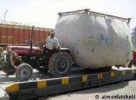 Um agricultor indiano pesa os resíduos da colheita, antes que sejam usados para produção de bionergia