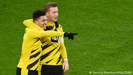 Jadon Sancho (left) and Marco Reus (right) smile after Sancho's second-half goal