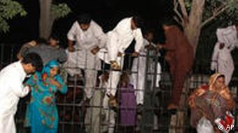 People jump over a fence to escape from Jinnah Hospital following an attack by gunmen in Lahore, Pakistan