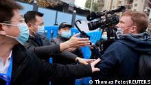 Sicherheitspersonal geht beim Besuch einer WHO-Delegation Ende Januar in Wuhan gegen ausländische Kameraleute vor