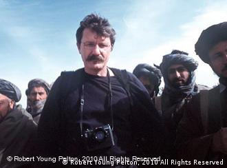 Robert Young Pelton surrounded by Hazara guard fighters, who tried to put down a revolt in Qali Jangi, Afghanistan in Nov. 2001