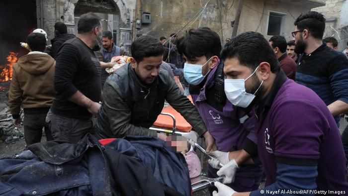 Rescue workers carry away a victim at the scene of an explosion in the town of Azaz, Syria