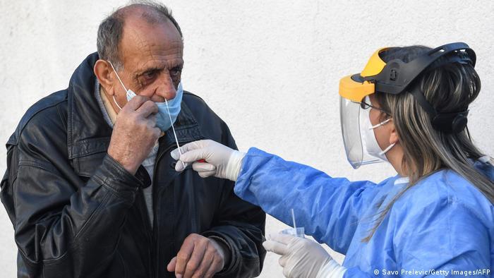 Eine jüngere Frau mit Plastik-Gesichtsschutz, Atemmaske, medizinischen Handschuhen und einem blauen medizinischem Umhang (rechts im Bild) schiebt einem älteren Mann mit Atemschutzmaske (links) einen Corona-Teststab in die Nase