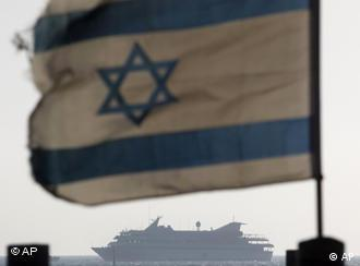An Israeli flag with one of the convoy's ships in the background