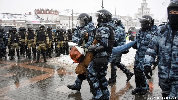 Police drag away a pro-Navalny protester in Moscow, Russia