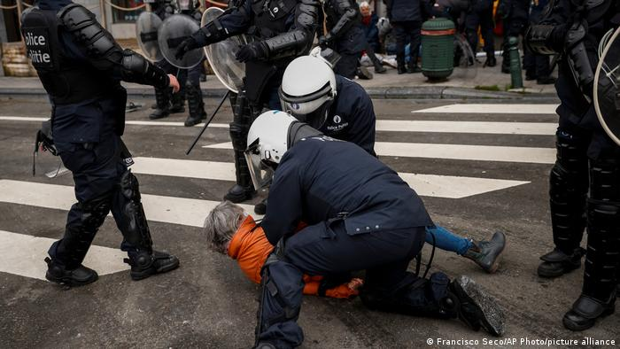 Brussels riot police hold down a protester