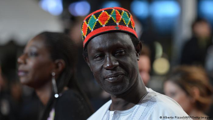 Moussa Toure, head shot of a man wearing a white shirt and a colorful hat