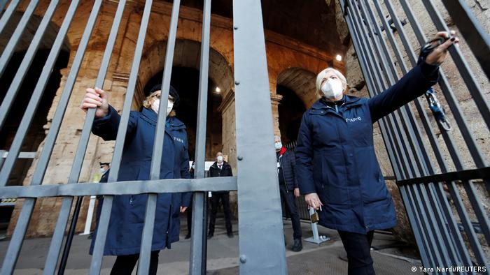 Two women open a gate at the Colosseum in Rome