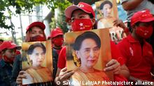 Burmese living in Thailand hold pictures of Myanmar leader Aung San Suu Kyi during a protest in front of the Myanmar Embassy in Bangkok, Thailand, Monday, Feb. 1, 2021. Myanmar's military has taken control of the country under a one-year state of emergency and reports say State Counsellor Aung San Suu Kyi and other government leaders have been detained. (AP Photo/Sakchai Lalit)