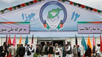 Some delegates leave the peace jirga tent after hearing sounds of a rocket attack
