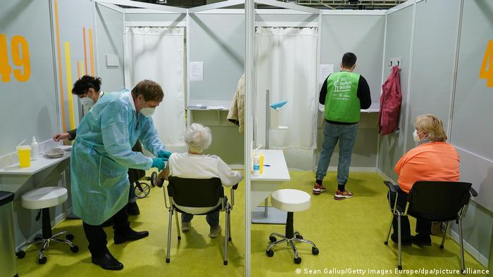 Two people seated with their backs to the camera await a COVID-19 vaccination