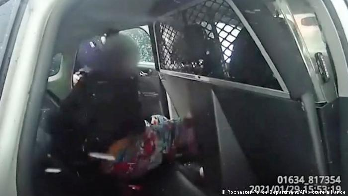 In this image taken on January 29, 2021 from the Rochester, NY Police Department body camera video, a nine-year-old girl is handcuffed in police custody in a police car after police use pepper spray on her as she screams at her.  father.