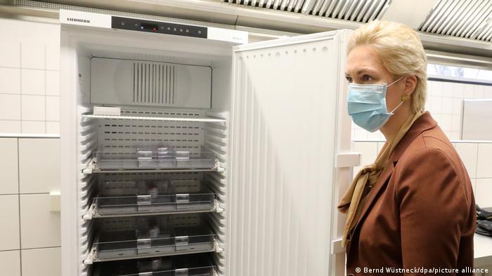 Die Ministerpräsidentin von Mecklenburg-Vorpommern, Manuela Schwesig steht mit Nase-Mund-Maske neben einem Kühlschrank, in dem der Impfstoff aufbewahrt werden soll