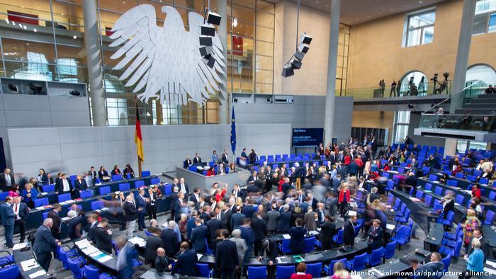 Blick in den Deutschen Bundestag, in dem sich Abgeordnete vor dem Rednerpult versammelt haben