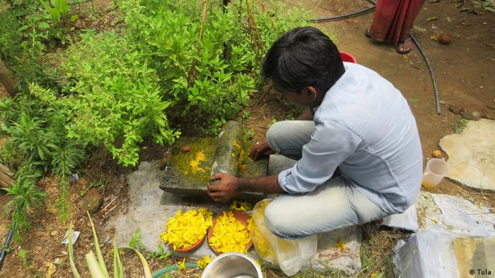 A man preparing yellow flowers to turn them into dye in Tamil Nadu, India