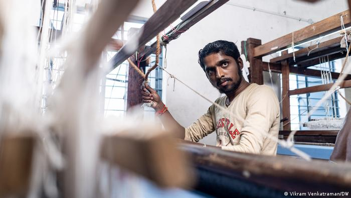 A man stands in front of a handloom in Tamil Nadu, India