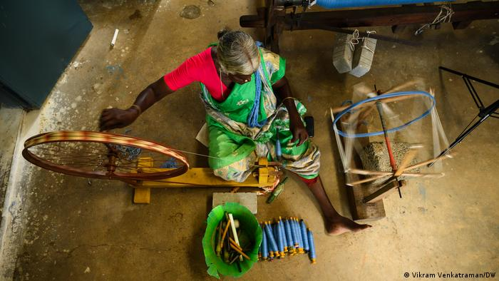 An indian woman in a green sari spins a handloom (seen from above)